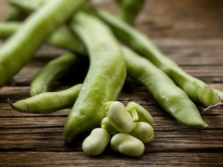 fresh beans broad over wood background, selective focus