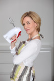 Profile view of blond woman holding electric whisk