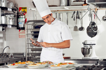 Male Chef Using Digital Tablet In Kitchen