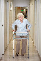 Elderly Woman With Walker In Hospital Corridor