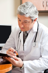 Mature Doctor Reading At Desk