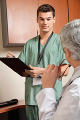 Technician With Doctor At Clinic