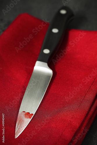Blutiges Küchenmesser auf einer roten Stoffserviette