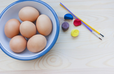 Easter eggs in a bowl, paints, brushes.