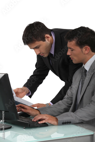 duo of male executives working on laptop