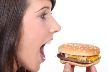 Brunette girl eating hamburger, profile-view