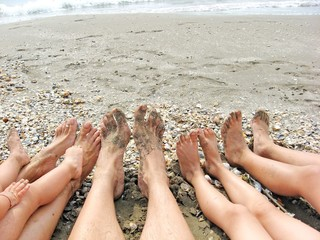 bare feet of a family on the shore