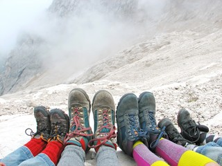 hiking boots of a family rest on the Dolomites