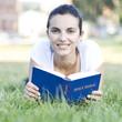woman reading bible on meadow