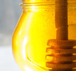 Golden honey in glass jar with wood dipper