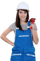 Happy female worker holding wrench