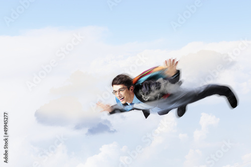 Young businessman flying with parachute on back