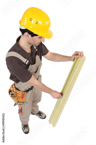 Carpenter measuring plank of wood