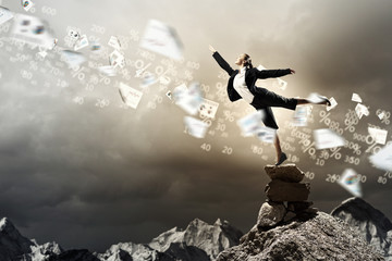 businesswoman standing atop of mountain