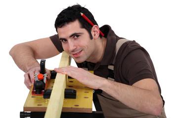 Carpenter eyeing a piece of wood