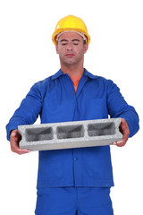 Builder carrying heavy building block