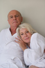 Retired couple sat in bathing robes
