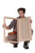 Carpenter displaying a wooden shutter