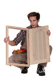Carpenter displaying a wooden shutter