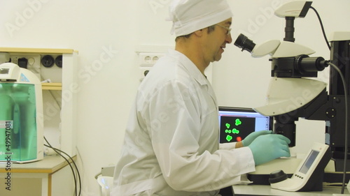 Scientific laboratory, man looking in microscope