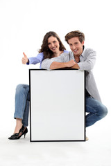 Couple crouching by empty frame