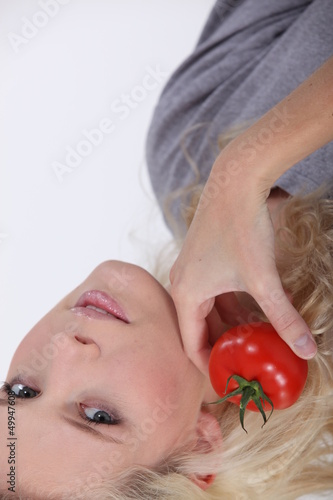 blonde woman posing with a tomato
