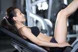 Woman at the gym doing exercises to strengthen muscles of legs poster