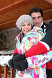 Couple hugging by their winter chalet