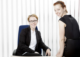 Two happy young women in an office