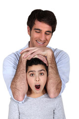 Man laying his arms over a surprised girl's head