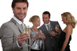 Man making a toast with champagne as his friends chat