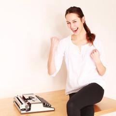 jubelndes Mädchen mit Schreibmaschine