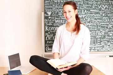 Schülerin mit Buch und Laptop