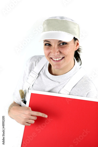 Happy female decorator pointing at red panel