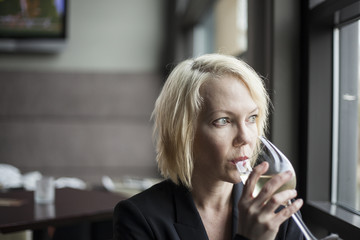Blonde Woman with Beautiful Blue Eyes Drinking Glass of White Wi