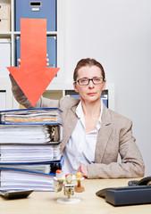 Strenge Frau zeigt mit Pfeil auf viele Akten