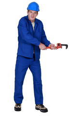 Tradesman trying to pull an object using a pipe wrench