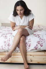 Frau mit Magen-Darm-Grippe auf dem Bett