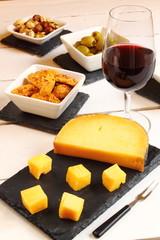 Aperitivo con vino, queso, aceitunas y galletas saladas
