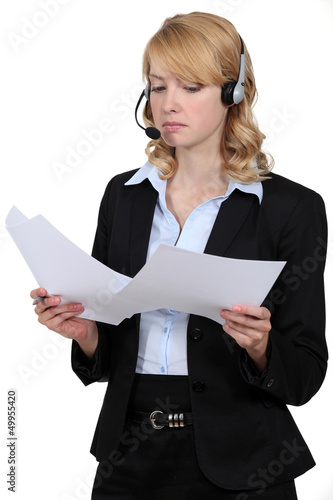 A blond businesswoman with a headset on.