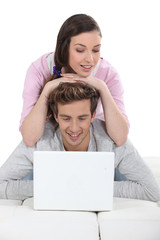 Affectionate couple using laptop together