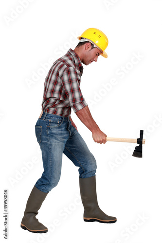 Tradesman using an axe to cut wood