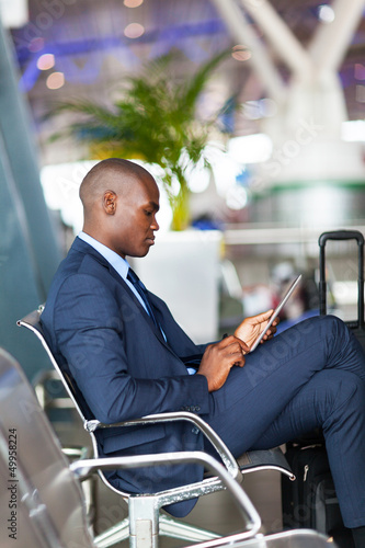 african american businessman using tablet computer at airport