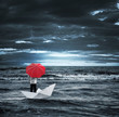 Man with a red umbrella on a paper boat in the stormy sea