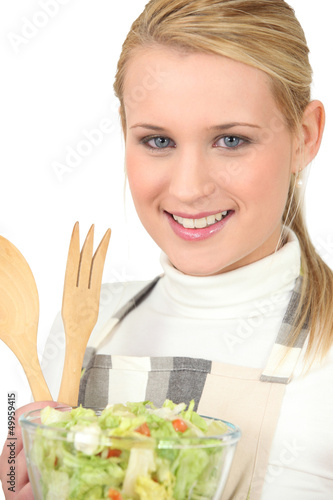 Blond girl eating green salad