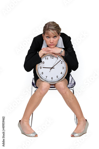 Businesswoman sitting with a large clock