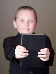 Boy holding book out