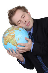 A businessman loving his globe.