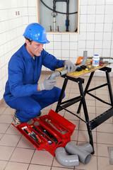 Plumber adjusting pipe