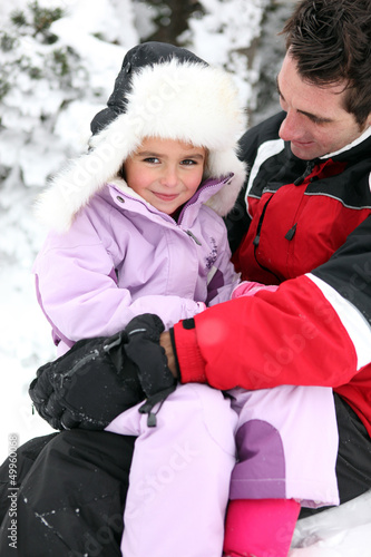 Father and daughter in snowsuits